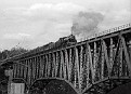 39-Steam engine pulling excursion train full of passengers across high bridge at New River in April 1979.